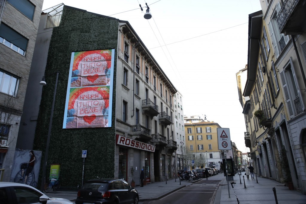 """In this photo taken on Friday, March 13, 2020, giant drawings of rainbows reading in Italian, """"Everything will be alright"""", hang on the side of a buil..."""