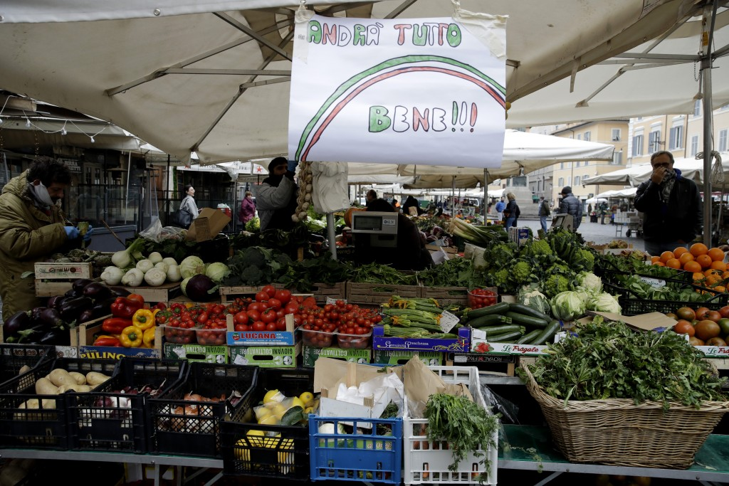 """In this photo taken on Friday March 13, 2020, a banner reading """"Everything will be alright"""" is placed at Rome's Campo Dei Fiori market. The nationwide..."""