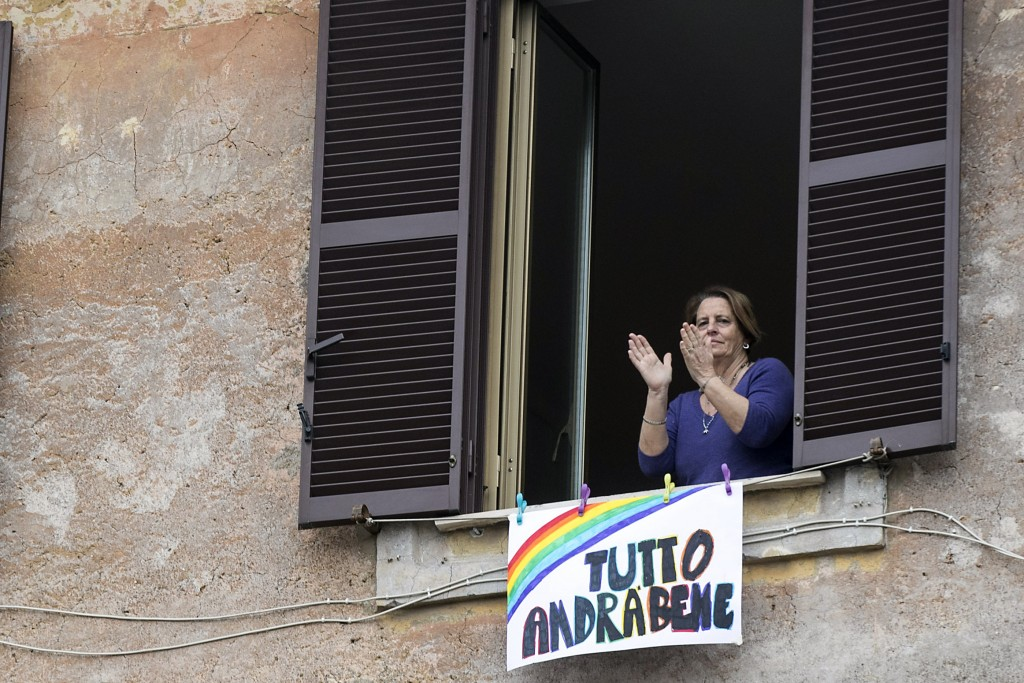 """In this photo taken on Saturday, March 14, 2020, a woman claps her hands next to a banner reading """"Everything will be alright"""", in Rome. The nationwid..."""