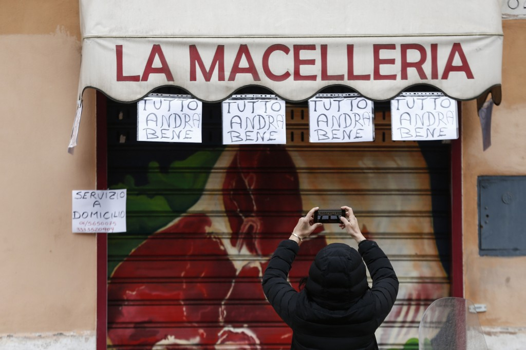 """In this Friday, March 13, 2020 image, a woman take photos of notes hanging from a butchery shop and reading in Italian """"Everything will be alright"""", i..."""