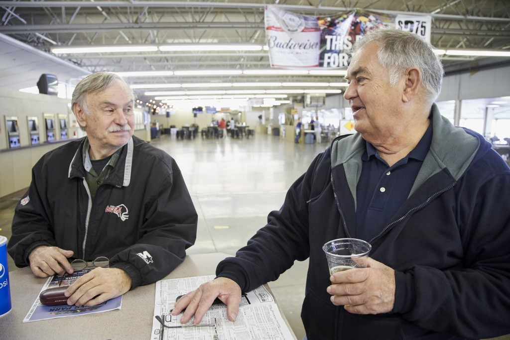 Ron Tenski and Jerry Moritz, right, who had arrived to Fonner Park in Grand Island, Neb., for the horse races, Saturday, March 14, 2020, prepares to l...