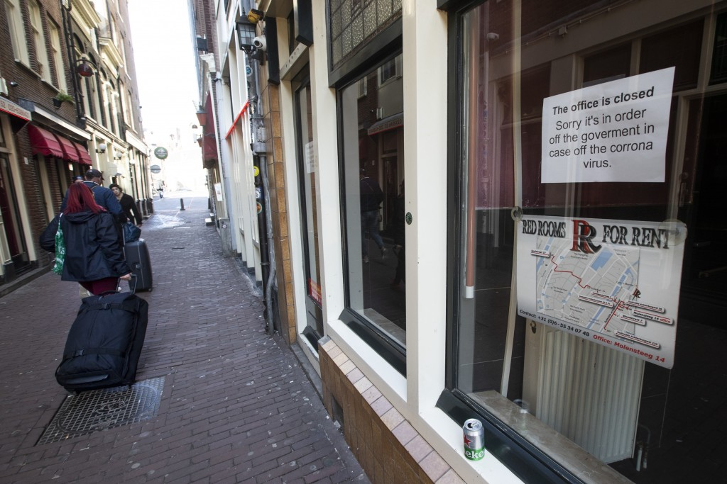 Two tourists pull their suitcases passing closed windows of sex workers in the Red Light District of Amsterdam, Netherlands, Monday, March 16, 2020. H...