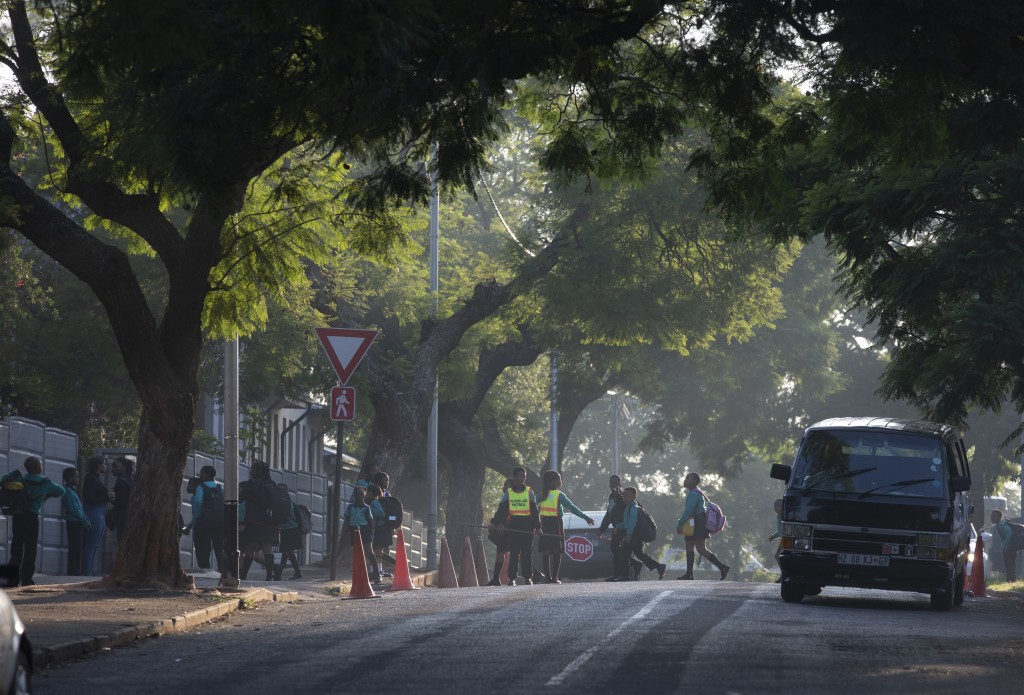 Children make their way to school in Johannesburg Monday, March 16, 2020 a day after President Cyril Ramaphosa declared a national state of disaster. ...