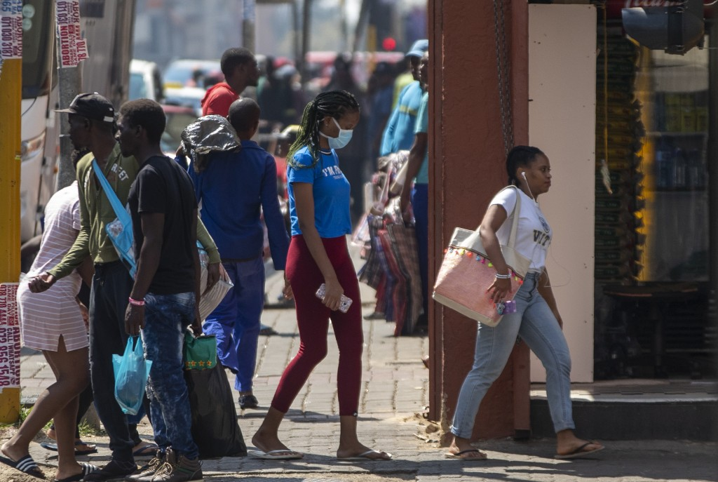 A woman wearing a face mask walks on a downtown street Johannesburg, South Africa, Monday, March 16, 2020. South African President Cyril Ramaphosa dec...