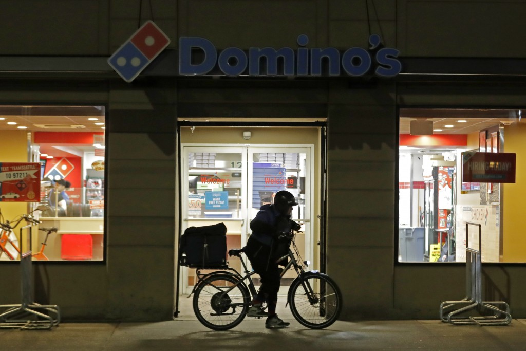 A delivery driver leaves a Domino's Pizza restaurant in downtown Seattle on a bike, Sunday, March 15, 2020. Washington Gov. Jay Inslee said Sunday nig...