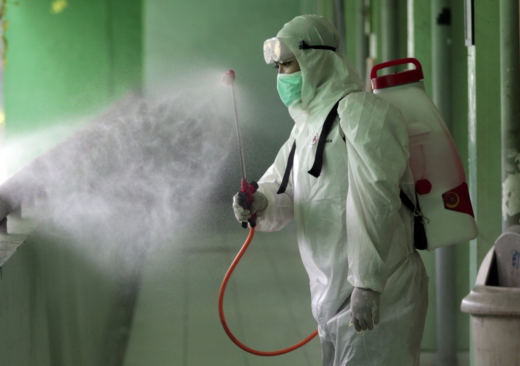 A member of Indonesian Red Cross sprays disinfectant in the wake of coronavirus outbreak at a school in Jakarta, Indonesia, Monday, March 16, 2020. In...