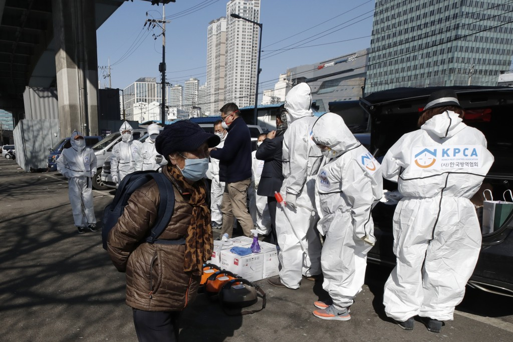 A woman wearing a face mask walks near workers wearing protective gears preparing to spray disinfectant as a precaution against the new coronavirus in...