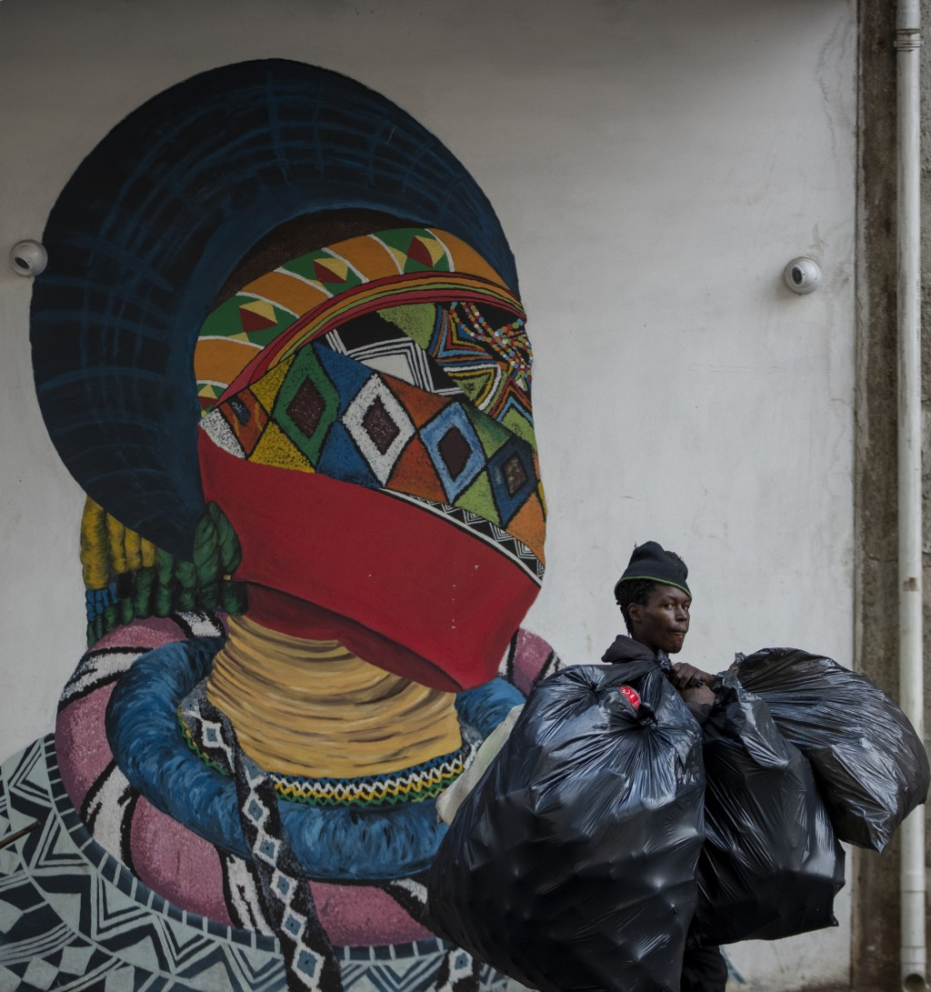 A man carrying plastic bags walks past a mural outside the Wits University school of art in Johannesburg, South Africa, Monday, March 16, 2020. South ...