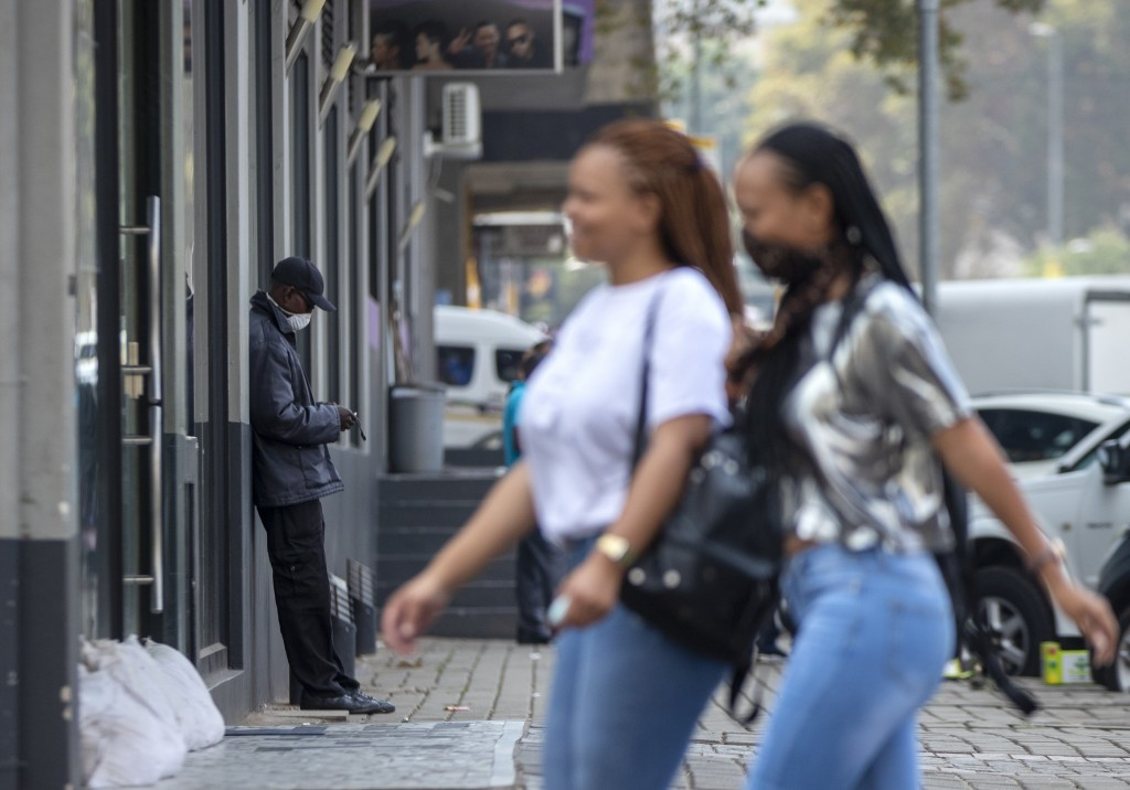 A man wearing a face mask leans against a building in a downtown street in Johannesburg, South Africa, Monday, March 16, 2020. South African President...