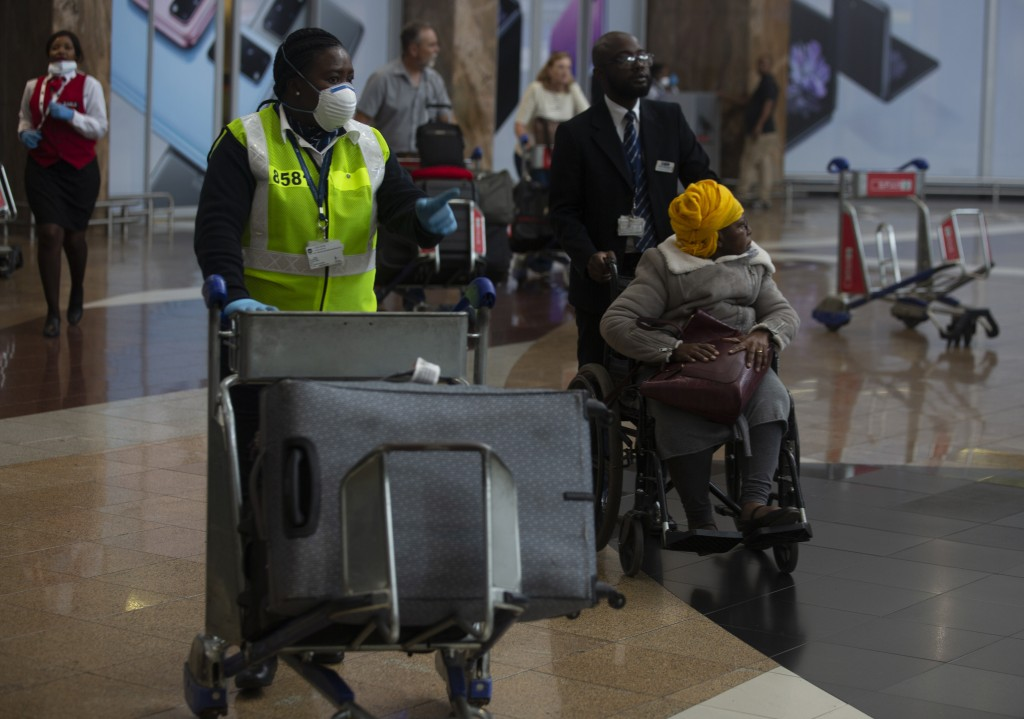 An elderly passenger arrives in a wheelchair at Johannesburg's O.R. Tambo International Airport, Monday, March 16, 2020, a day after President Cyril R...