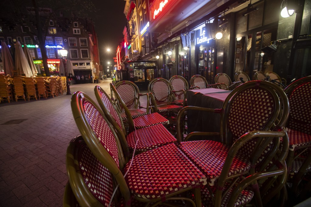 The bars are closed and terrace chairs are stacked on the popular Leidseplein in Amsterdam, Netherlands, Sunday, March 15, 2020, after a TV address of...