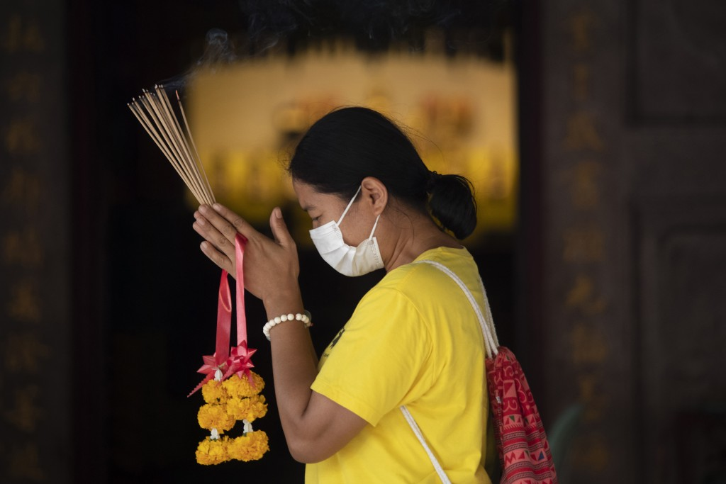 A woman wears a protective mask as she offers incenses during prayers at the Leng Nuei Yee Chinese temple in Bangkok, Thailand, Monday, March 16, 2020...