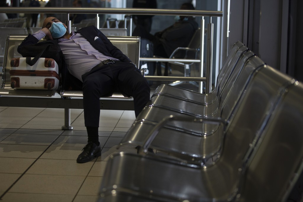 A traveller wearing a mask sits in Johannesburg's O.R. Tambo International Airport, Monday, March 16, 2020, a day after President Cyril Ramaphosa decl...
