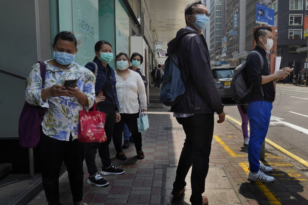 People wearing face masks walk at a down town street in Hong Kong Monday, March 16, 2020. For most, the coronavirus causes only mild or moderate sympt...