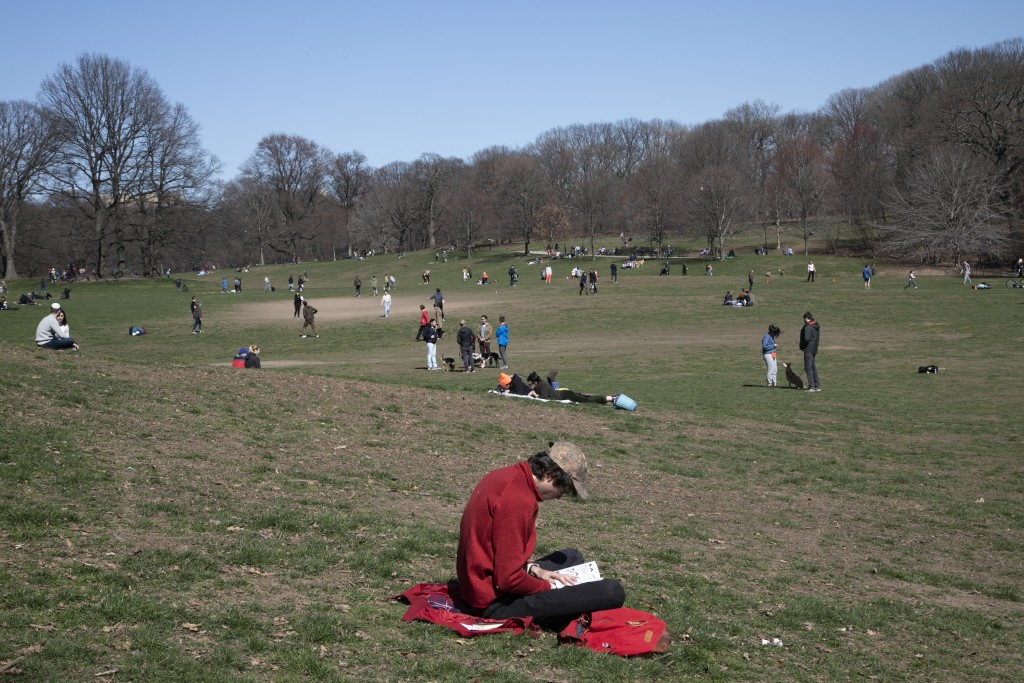 A man reads his book in Prospect Park in the Brooklyn borough of New York on Sunday, March 15, 2020. President Donald Trump on Sunday called on Americ...