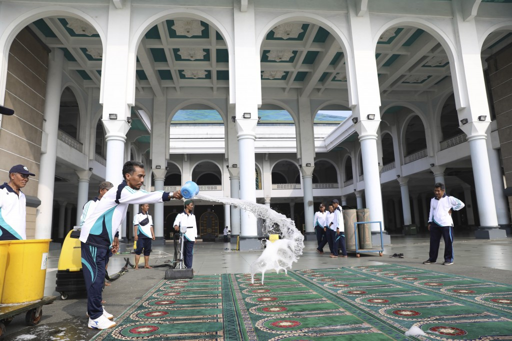 Staff douse praying mats with disinfectant in the wake of coronavirus outbreak at Al Akbar mosque in Surabaya, Indonesia, Monday, March 16, 2020. For ...