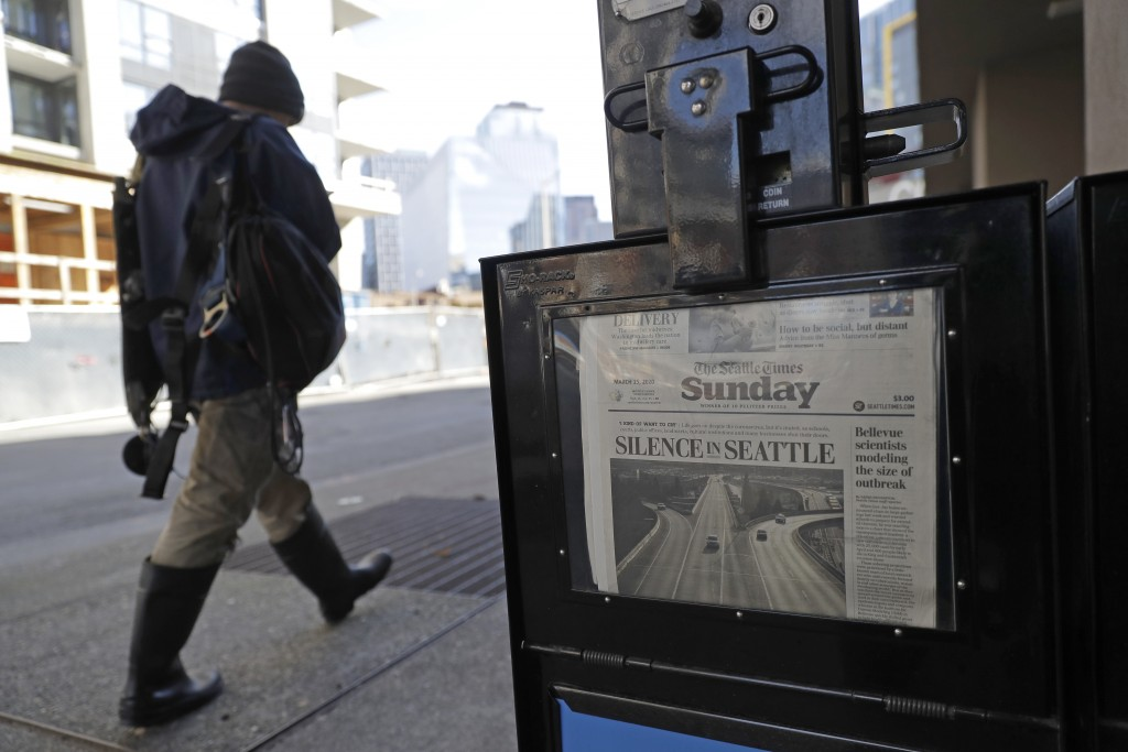 A man walks near a Seattle Times newspaper box in front of the building that houses the Times' newsroom, Sunday, March 15, 2020 in Seattle, as the hea...
