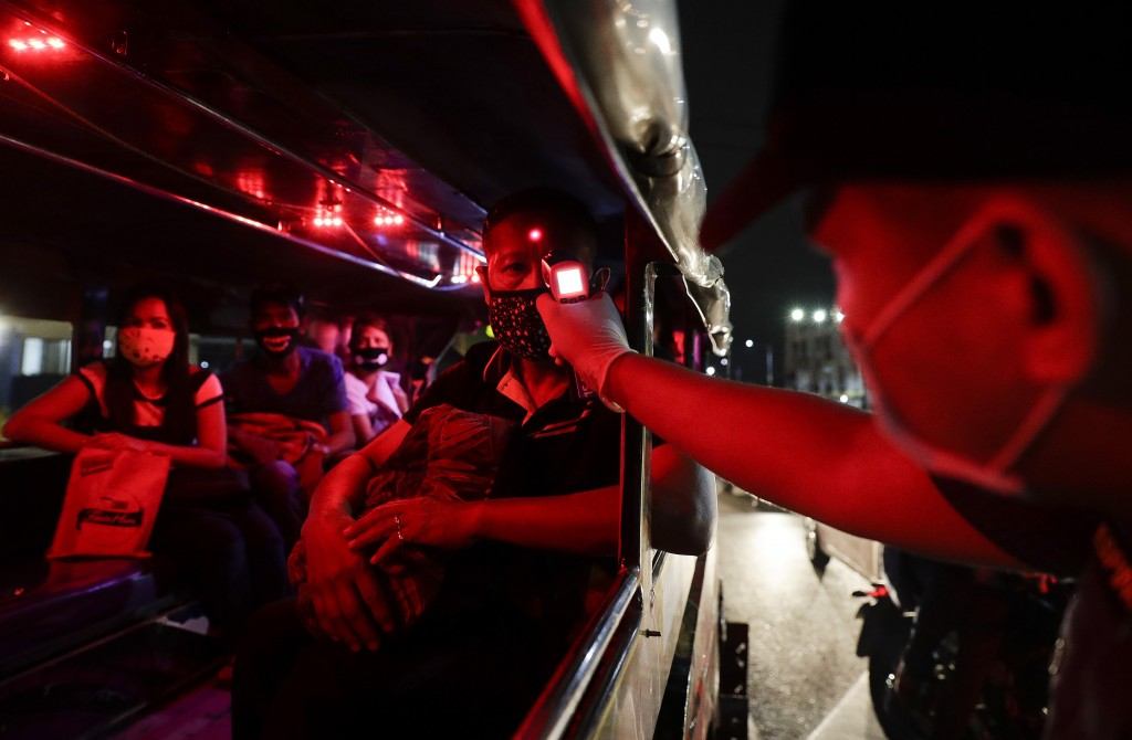 A police officer checks the temperatures of passengers inside a jeepneyin Manila, Philippines.