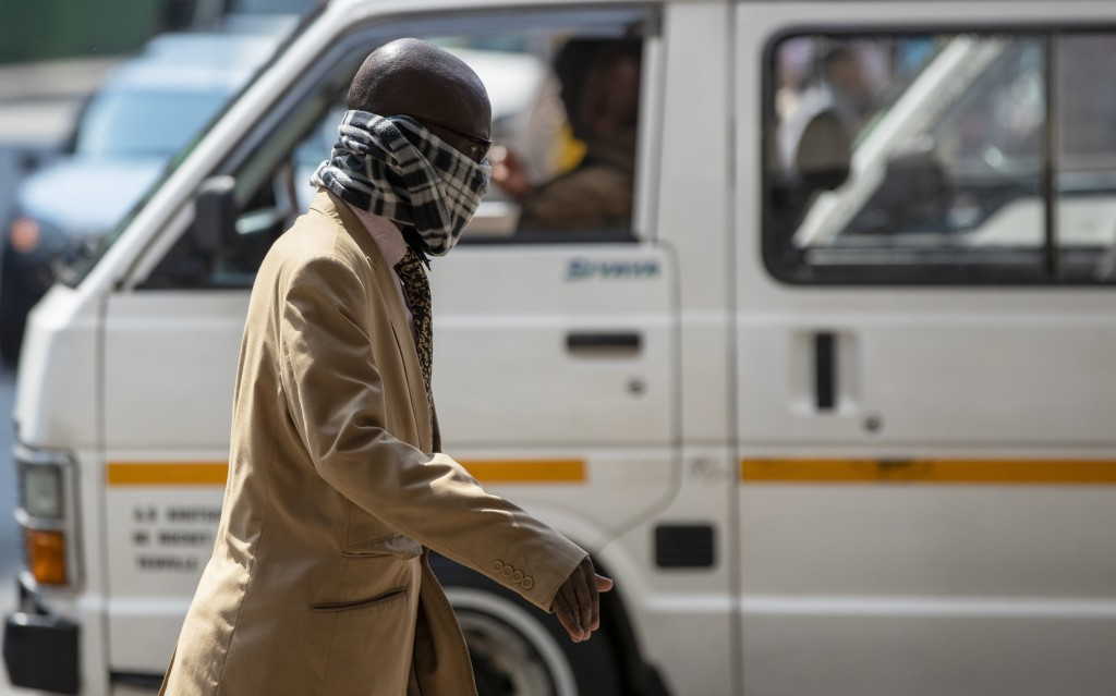 A man using a scarf to cover his face walks along a downtown street Johannesburg, South Africa, Monday, March 16, 2020. South African President Cyril ...