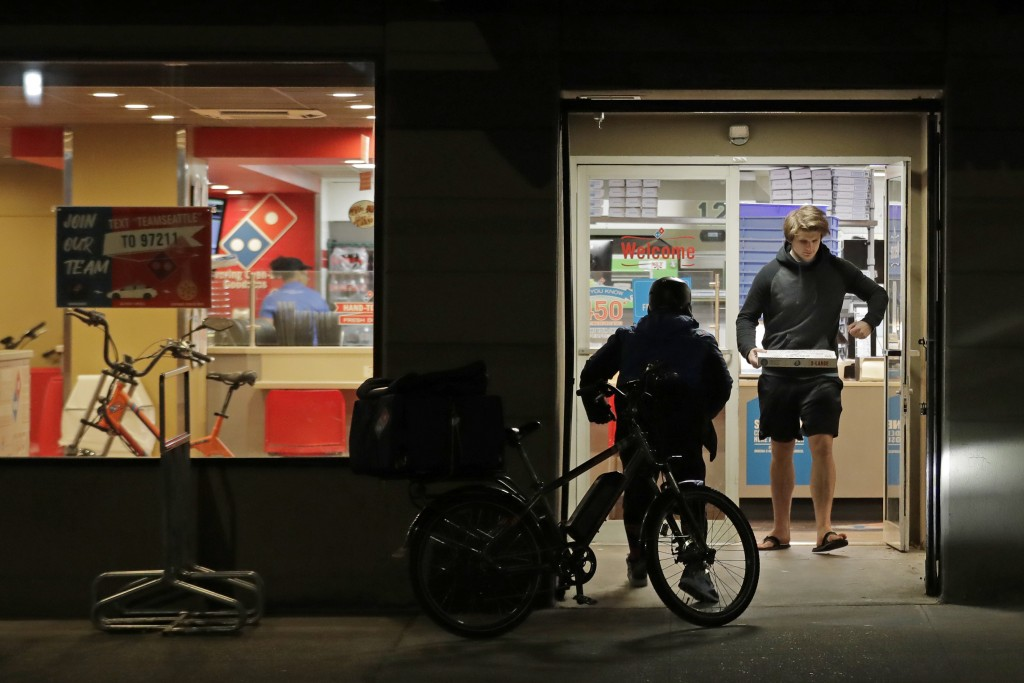 A man uses his elbow to open the door as he walks out of a Domino's Pizza restaurant in downtown Seattle as a delivery driver walks in, Sunday, March ...