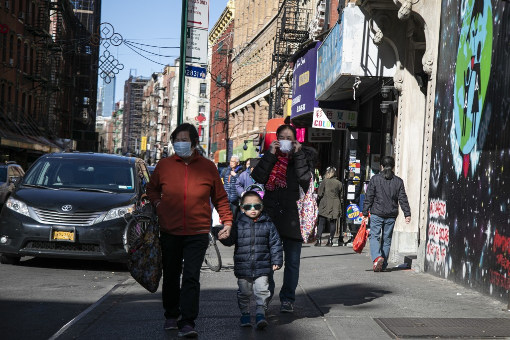 People wear face masks as they walk down the street in Chinatown in New York, on Sunday, March 15, 2020. President Donald Trump on Sunday called on Am...