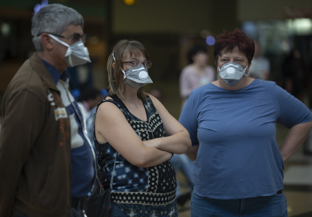 People wearing masks wait for passengers at Johannesburg's O.R. Tambo International Airport, Monday, March 16, 2020 a day after President Cyril Ramaph...