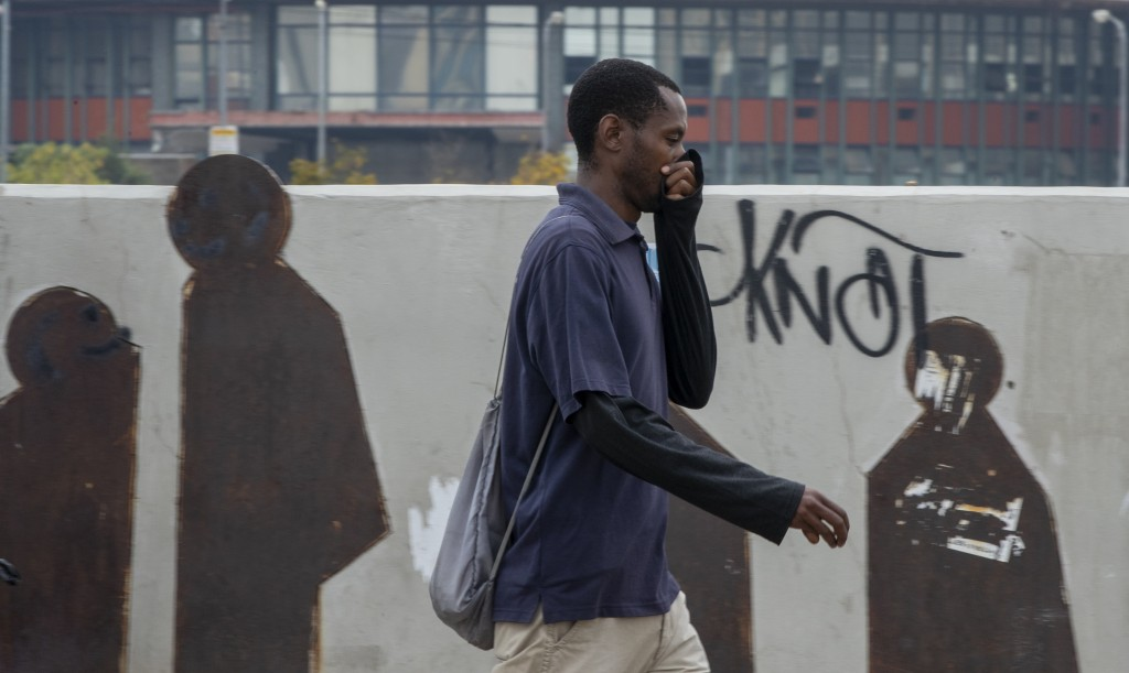 A man uses his hand to cover his nose as he walks along a downtown street Johannesburg, South Africa, Monday, March 16, 2020. South African President ...