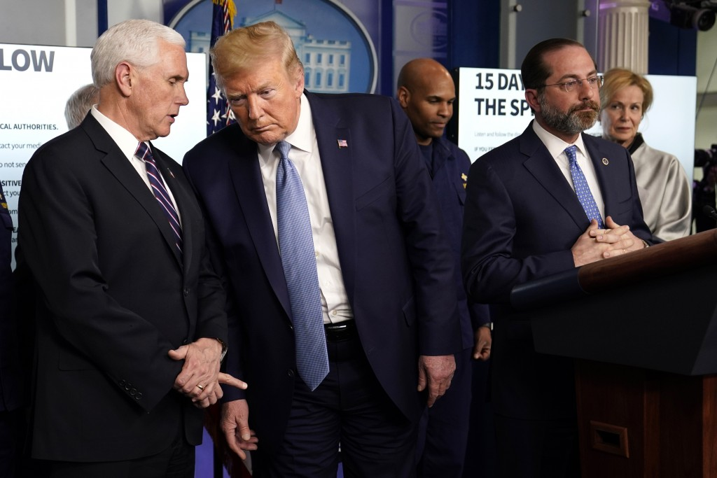President Donald Trump listens to Vice President Mike Pence, left, as Health and Human Services Secretary Alex Azar speaks during a press briefing wit...