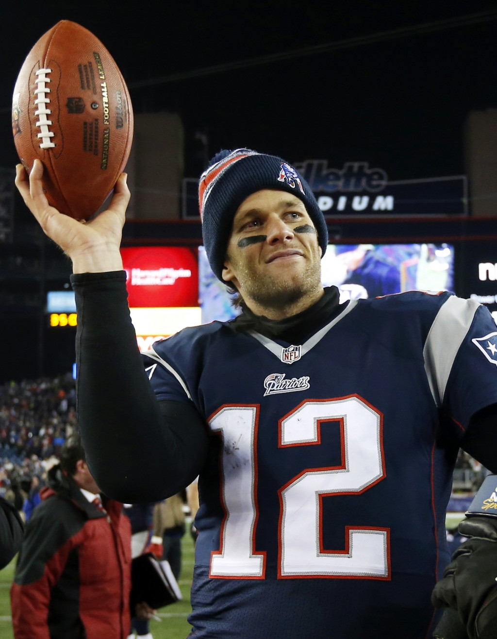 FILE - In this Jan. 10, 2015, file photo, New England Patriots quarterback Tom Brady holds up the game ball after an NFL divisional playoff football g...