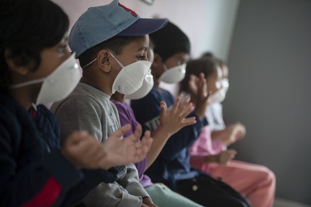 Learners wear masks as they sanitise their hans at a pre-school in Lenasia, Johannesburg, Tuesday, March 17, 2020, on the day schools closed in a bid ...