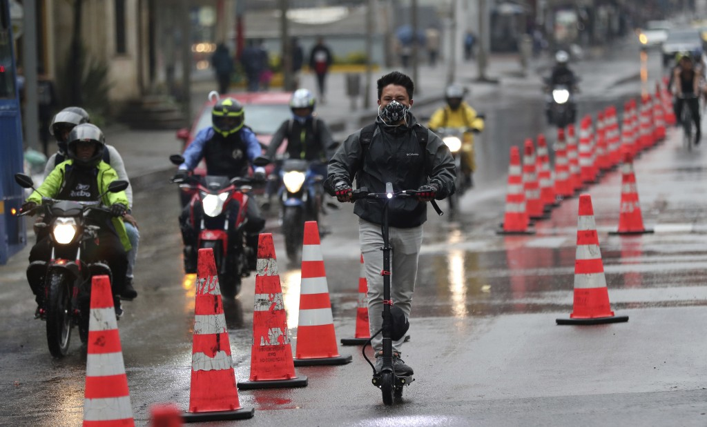 A man wearing a protective mask rides his electric scooter in a bike lane, in Bogota, Colombia, Monday, March 16, 2020. Officials in Colombia's capita...