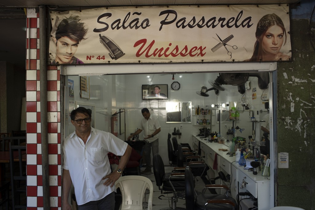 A hairdresser waits for customers at his shop in the the Rocinha slum of Rio de Janeiro, Brazil, Monday, March 16, 2020. Since the outbreak of the new...