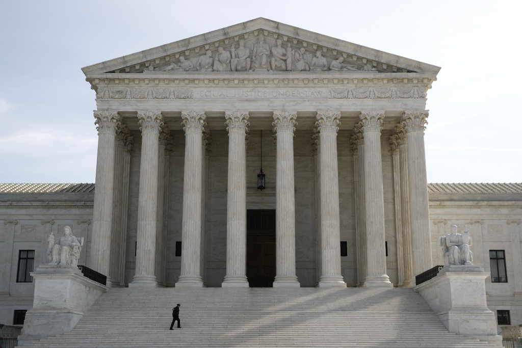 A police officer walks outside the Supreme Court in Washington, Monday, March 16, 2020. The Supreme Court announced Monday that it is postponing argum...
