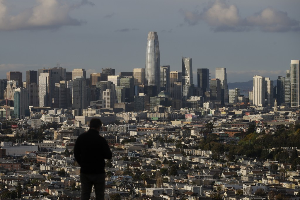 A man looks toward the skyline from Bernal Heights Hill in San Francisco, Monday, March 16, 2020. Officials in six San Francisco Bay Area counties iss...
