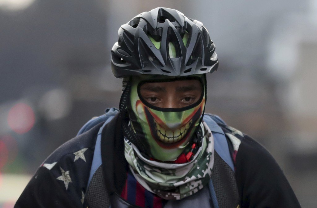 A man, wearing a stylized mask, rides his bicycle in Bogota, Colombia, Monday, March 16, 2020. Officials in Colombia's capital have expanded bike rout...