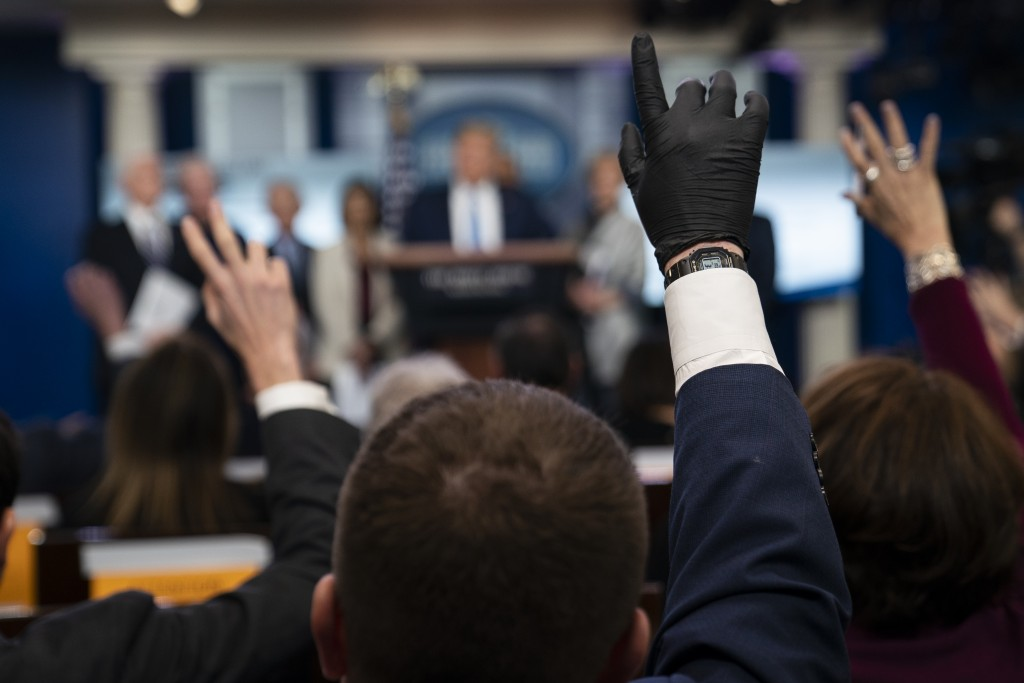 Reporters raise their hands to ask President Donald Trump questions during a press briefing with the coronavirus task force, at the White House, Monda...