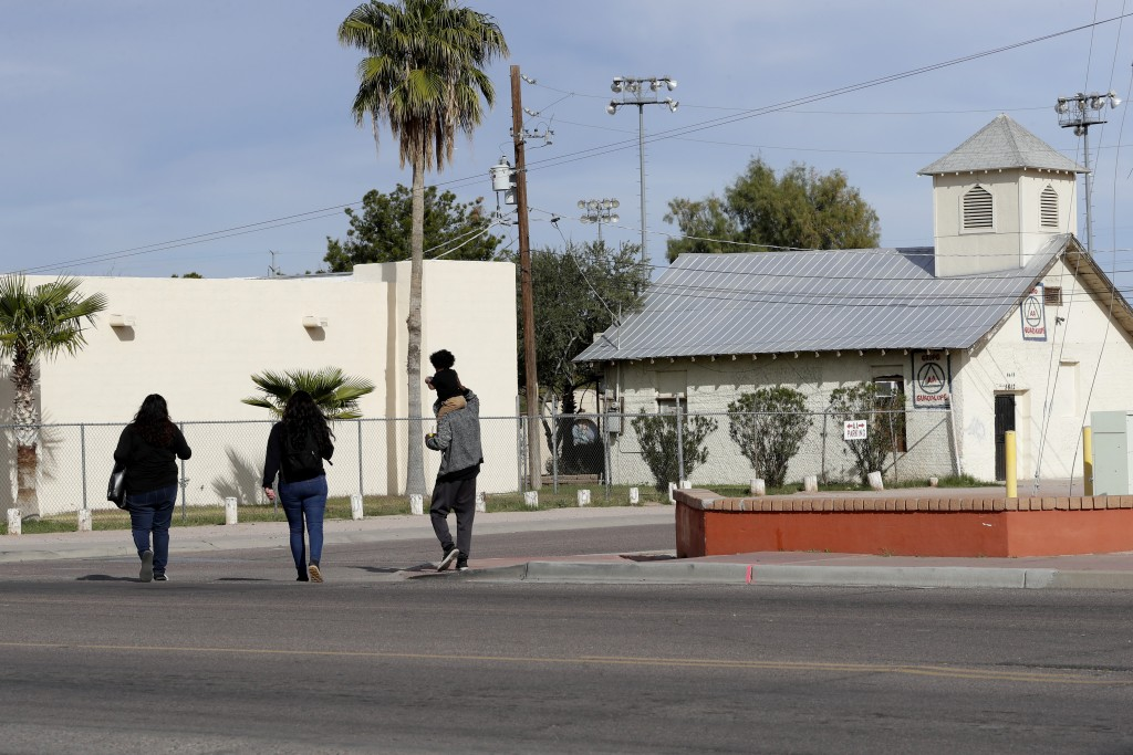 People walk Friday, Jan. 24, 2020 in Guadalupe, Ariz. Founded by Yaqui Indian refugees from Mexico more than a century ago, Guadalupe is named for Mex...