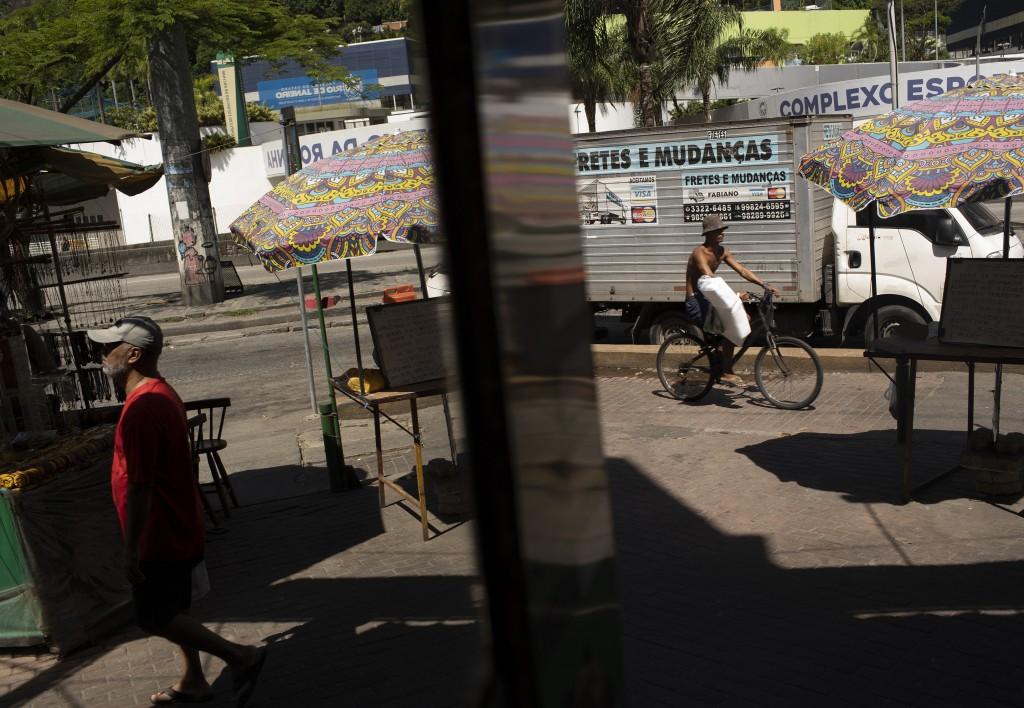 Residents move in Rio de Janeiro's Rocinha slum in Brazil, Monday, March 16, 2020. Since the outbreak of the new coronavirus, nations have begun impos...