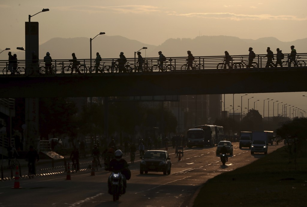 Commuters walk their bicycles across a pedestrian bridge, in Bogota, Colombia, Tuesday, March 17, 2020. Officials in Colombia's capital have expanded ...