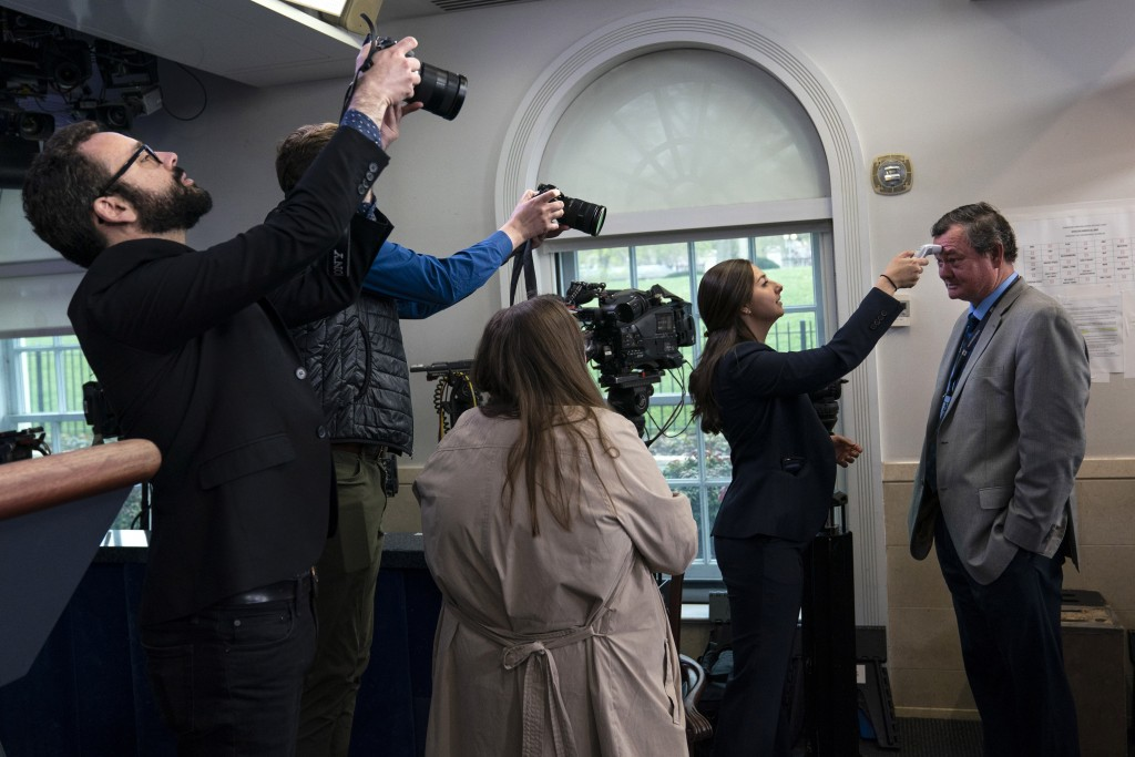 ADDS ID - Associated Press journalist Kevin Freking has his temperature checked before a coronavirus task force briefing, at the White House, Tuesday,...