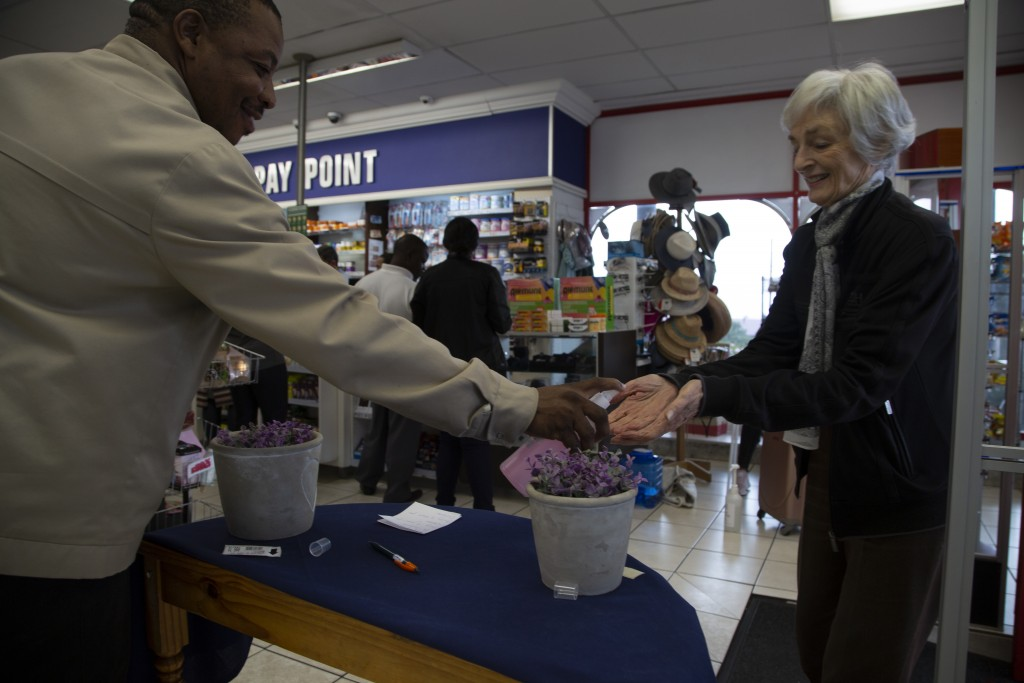 A customer sanitises her hands on entering a pharmacy in Johannesburg Tuesday, March 17, 2020, in a bid to control the spread of coronavirus. For most...