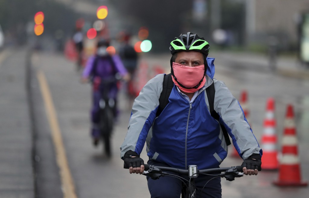 A man wearing a protective mask rides his bicycle in Bogota, Colombia, Monday, March 16, 2020. Officials in Colombia's capital have expanded bike rout...