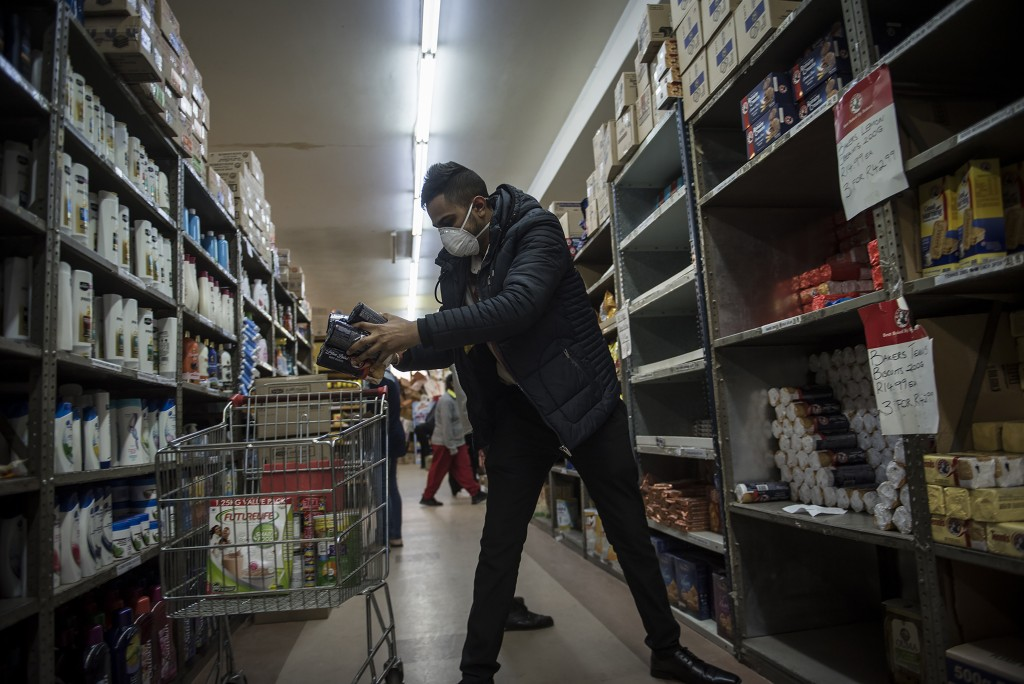 A man stocks up on groceries at a supermarket in Lenasia, Johannesburg, South Africa, Tuesday March 17, 2020. For most people the virus causes only mi...