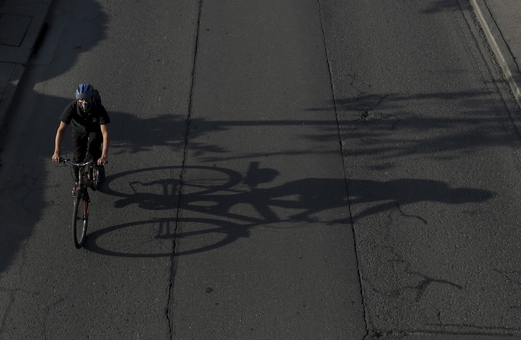 A man, wearing protective mask, rides his bicycle in Bogota, Colombia, Tuesday, March 17, 2020. Officials in Colombia's capital have expanded bike rou...