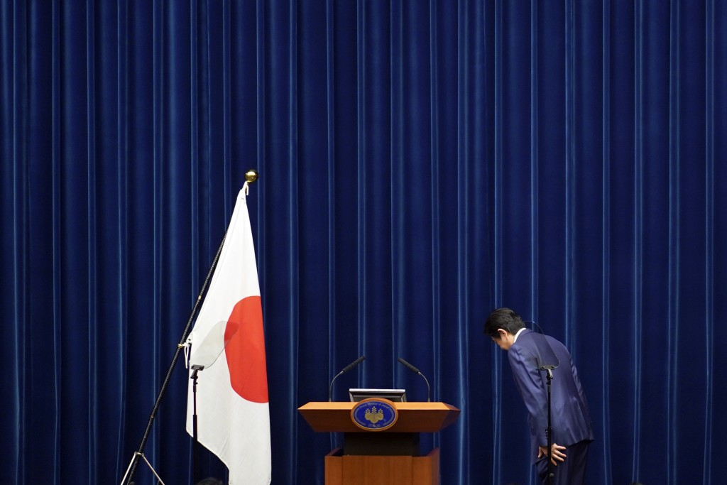 FILE - In this March 14, 2020, file photo, Japanese Prime Minister Shinzo Abe bows to toward a Japanese flag before delivering his speech at the Prime...