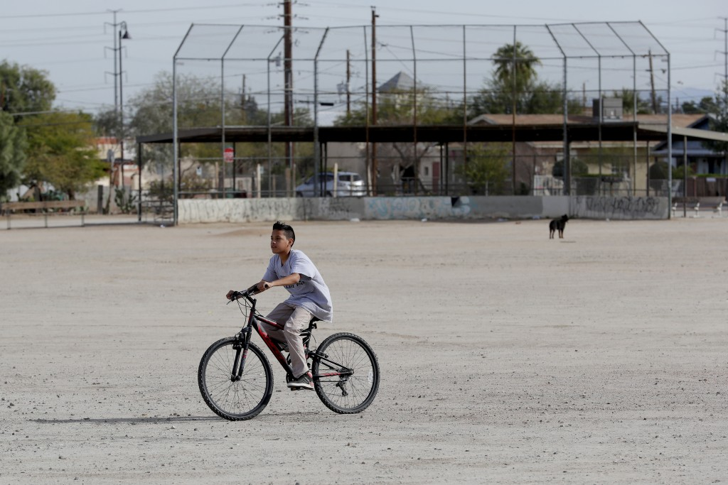 A boy rides his bike Friday, Jan. 24, 2020 in Guadalupe, Ariz. Founded by Yaqui Indian refugees from Mexico more than a century ago, Guadalupe is name...