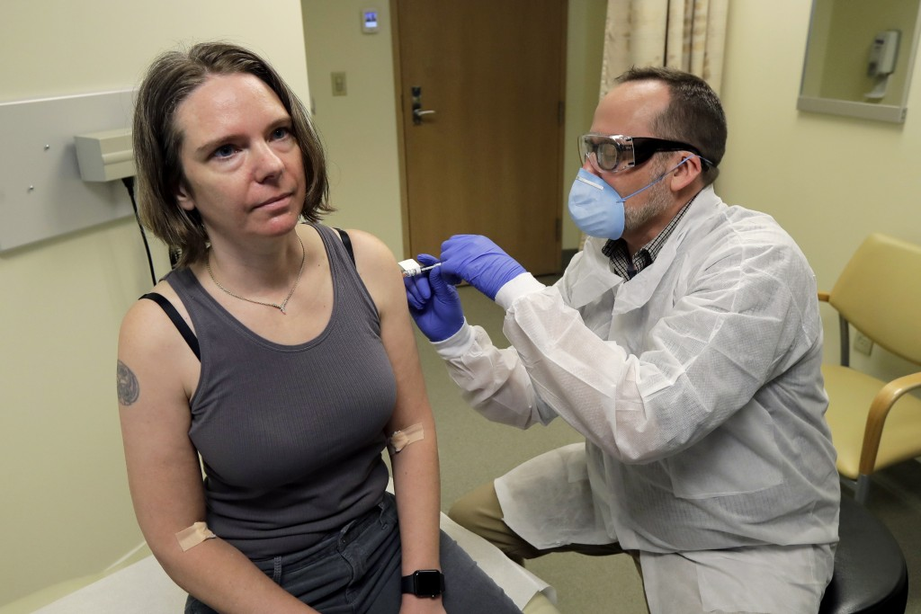 A pharmacist gives Jennifer Haller, left, the first shot in the first-stage safety study clinical trial of a potential vaccine for COVID-19, the disea...