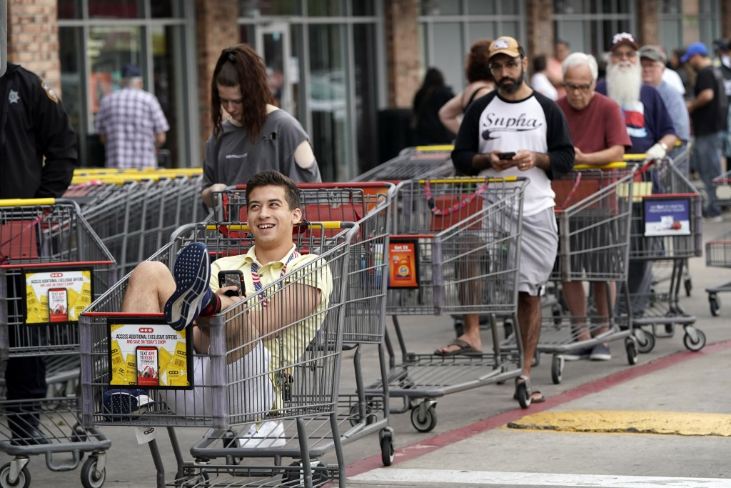 John Sinoski sits in a shopping cart while waiting for an H-E-B grocery store to open Tuesday, March 17, 2020, in Spring, Texas. Sinoski, who arrived ...