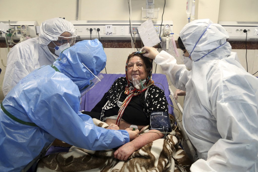 FILE— In this Sunday, March 8, 2020 file photo, medics treat a patient infected with the new coronavirus, at a hospital in Tehran, Iran. Nine out of 1...