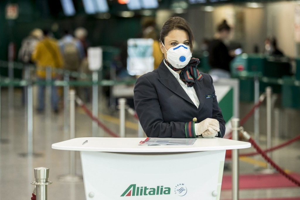 An Alitalia employee waits at the desk the Leonardo Da Vinci airport, in Rome, Tuesday, March 17, 2020. For most people, the new coronavirus causes on...
